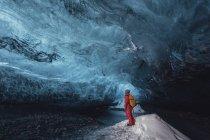 Человек смотрит в ледяную пещеру, ледник Ватнайокалл, Национальный парк Ватнайокалл, Исландия — стоковое фото
