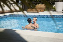 Heterosexual couple in swimming pool together, face to face — Stock Photo