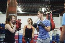 Entraînement de boxeur masculin, prêt à frapper ses coéquipiers punch mitt — Photo de stock