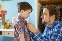 Vater hilft Sohn Knopfhemd im Schlafzimmer — Stockfoto