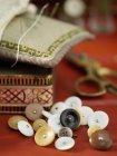 Boutons vintage et coussin de broche sur la table rouge — Photo de stock