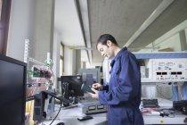 Panneau de commande de réparation d'électricien masculin en atelier — Photo de stock