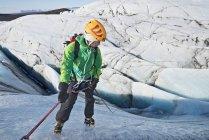 Mature female climber rappelling down glacier wall, Svinafellsjokull, Vatnajokull National Park, Iceland — Stock Photo