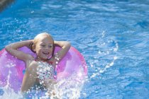 Girl lying on her back on inflatable ring in garden swimming pool — Stock Photo