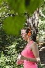Молода жінка проходить через лісистого парку — стокове фото