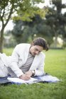 Businessman reclining on picnic blanket writing notes in park — Stock Photo