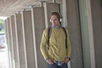 Mid adult man listening to headphones in city underpass — Stock Photo