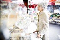 Зрілі жінки shopper купівлі сиру в місцевих французькому ринку — стокове фото