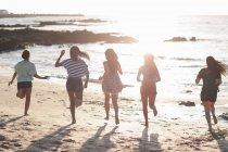 Вид сзади женщины, работающие вместе на пляже — стоковое фото