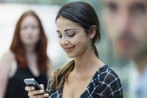 Donna che usa il telefono, colleghi in background — Foto stock