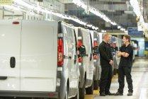 Kfz-Lehrlinge unterhalten sich in Autofabrik neben Kastenwagen-Karossen — Stockfoto