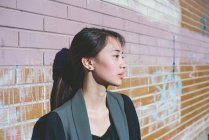 Portrait of young woman leaning against graffiti brick wall — Stock Photo