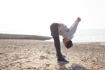 Jovem treinando, curvando-se para frente na praia de Brighton — Fotografia de Stock