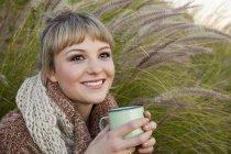 Portrait de jeune femme parmi les hautes herbes avec la tasse de boissons — Photo de stock