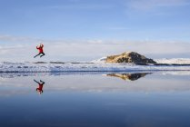 Woman jumping beside lake, Markarfljot, Iceland — Stock Photo