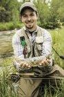 Человек, стоящий на коленях на берегу реки, держит свежепойманную рыбу, смотрит в камеру и улыбается. — стоковое фото