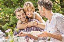 Gruppo di amici che si godono la festa in giardino, giovane donna che abbraccia il giovane — Foto stock