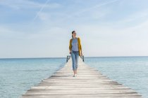 Mid adult woman walking along pier — Stock Photo