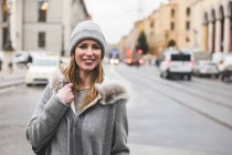 Portrait of mid adult woman in knit hat on city street — Stock Photo