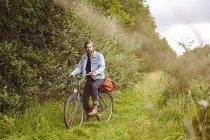 Portrait of mid adult man on bicycle on rural path — Stock Photo