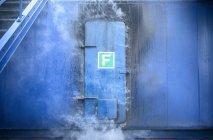 Smoke from fire behind steel door — Stock Photo