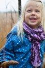 Sonriente chica de pie en la hierba alta - foto de stock