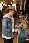 Young man looking at clothes in clothes shop — Stock Photo