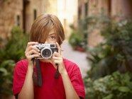 Портрет мальчика, фотографирующего деревню с помощью камеры SLR, Мальорка, Испания — стоковое фото