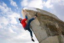 Climber free climbing snow capped peak — Stock Photo