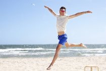 Young man leaping mid air on beach, Port Melbourne, Melbourne, Australia — Stock Photo