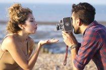 Giovane uomo riprese donna con fotocamera vintage — Foto stock