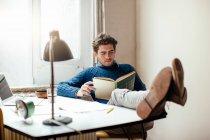 Junger Mann Lesebuch mit Füßen oben auf Schreibtisch — Stockfoto