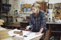 Young craftswoman checking components on workbench in pipe organ workshop — Stock Photo