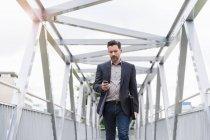 Mature businessman walking on footbridge texting on smartphone — Stock Photo