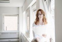 Mulher de negócios adulta média lendo papelada no escritório — Fotografia de Stock