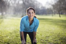 Portrait of young woman taking training break in park — Stock Photo