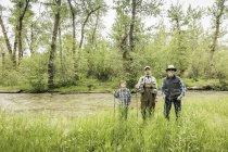 Vue de face du multi génération famille debout sur berge tenant des cannes à pêche — Photo de stock