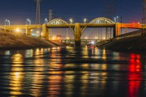 Diminishing perspective of Los Angeles river and 6th street bridge illuminated at night — Stock Photo
