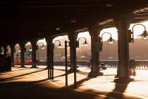 Тени и lamposts ниже моста на закате — стоковое фото