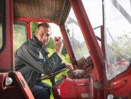 Agriculteur en tracteur mangeant des pommes — Photo de stock