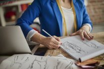 Cropped view of woman sitting at desk sketching fashion design — Stock Photo