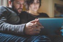 Casal sentado no sofá, olhando para tablet digital — Fotografia de Stock