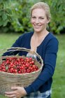 Woman carrying basket of cherries — Stock Photo