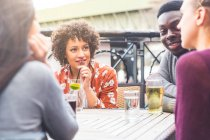 Friends in beer garden at table enjoying a drink, smiling — Stock Photo