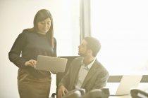 Средние коллеги по бизнесу обсуждают за ноутбуком в офисе — стоковое фото