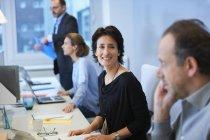 Uomini e donne d'affari seduti alla scrivania in ufficio — Foto stock