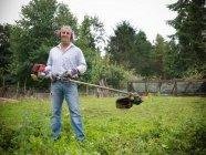 Портрет садовника с защитными ушами и козырьком, удерживающим стриммер — стоковое фото