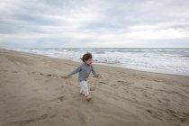 Mädchen läuft am Strand von Ozean — Stockfoto