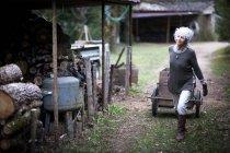 Mature woman pulling handcart in garden — Stock Photo