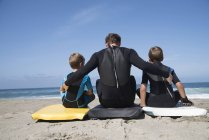 Rear view of man and two sons sitting on bodyboards, Laguna Beach, California, USA — Stock Photo